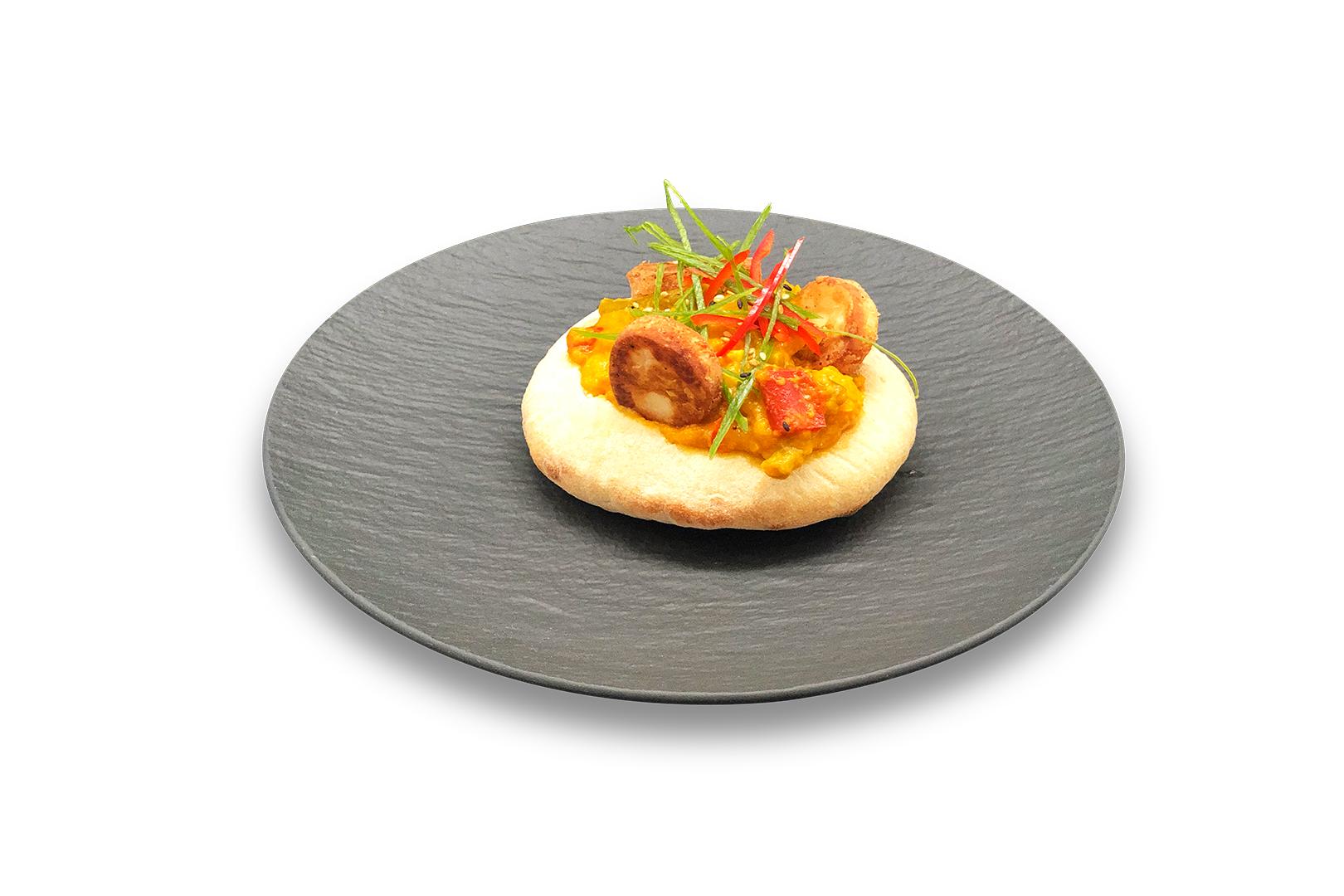 Open pizza bol geserveerd met gele curry krokante halloumi, bosui en rode peper