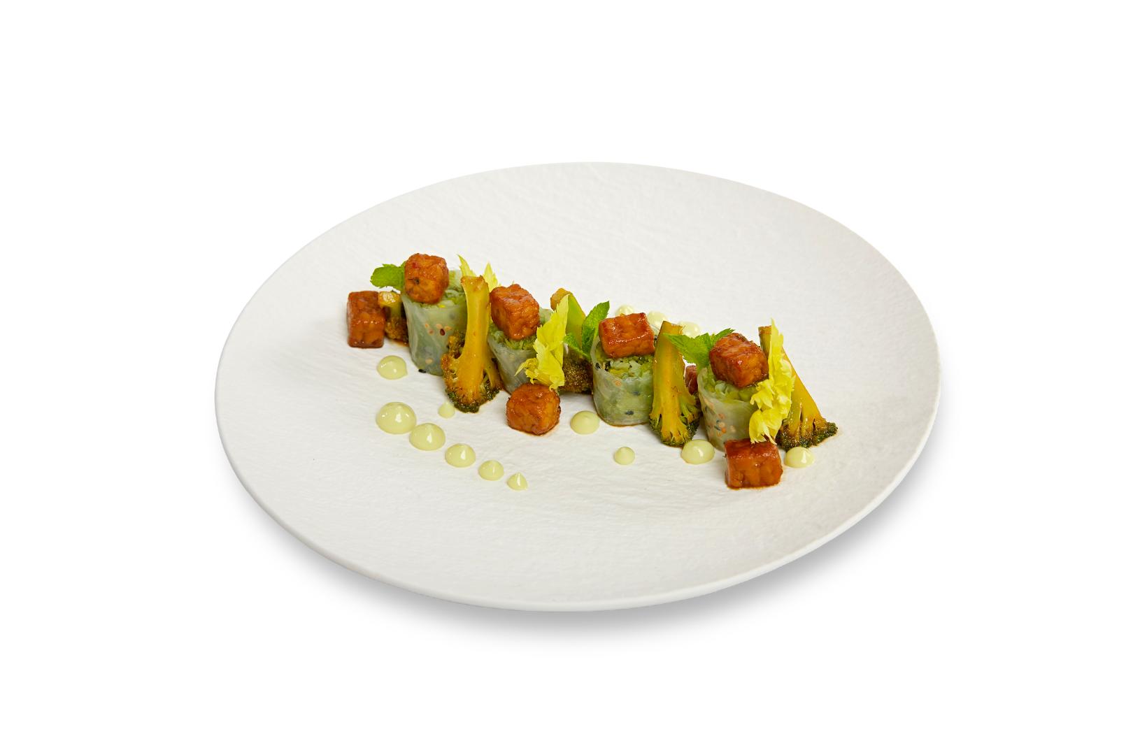 Springroll gevuld met Griekse Witte Kool, geblancheerde peultjes, zeewier en venkel. Geserveerd met geglaceerde roergebakken broccoli