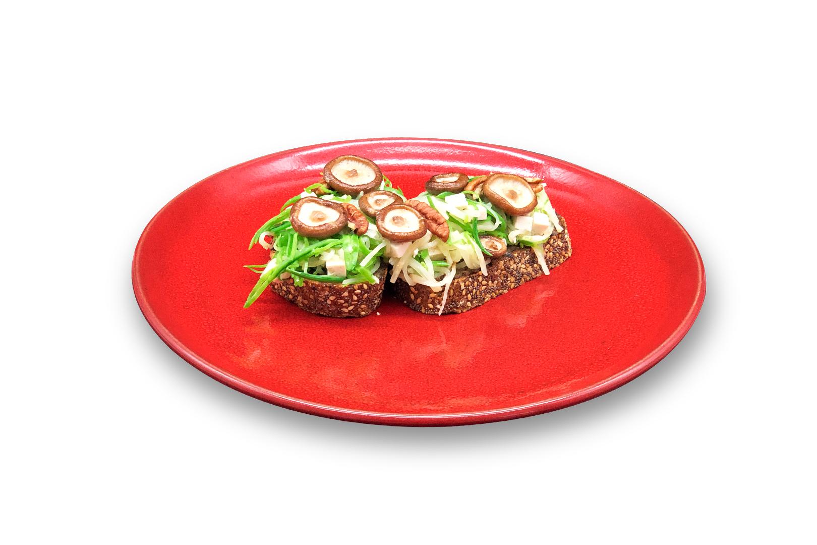 Toast met truffel tapenade, knisperige salade van geblancheerde knolselderij en peultjes geserveerd met tofu en gebakken Shiitaken