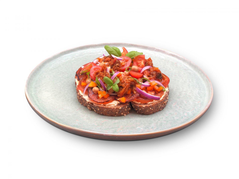Vegan brood met humus, bruschetta en gebrande tomaat, bovenop een salade gemaakt van kikkererwten, snoeptomaatjes, rode ui en bosui